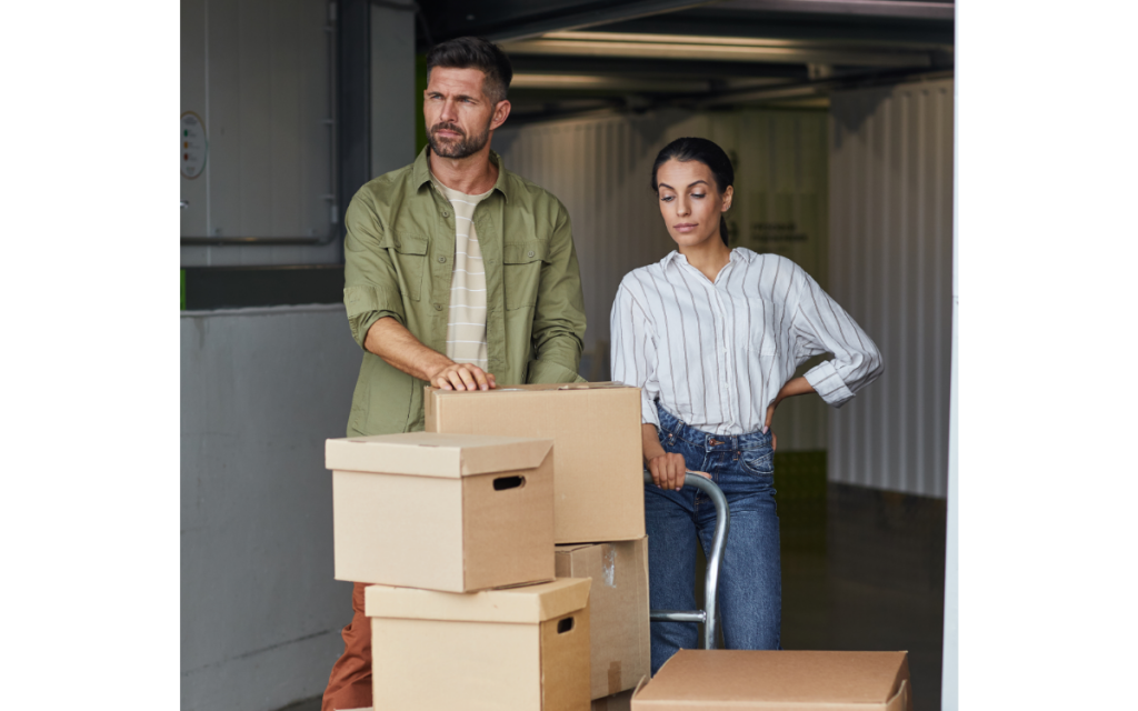 couple with boxes on cart at storage facility