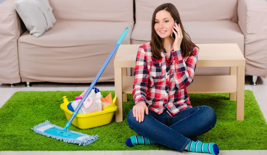 girl-on-the-phone-while-resting-after-cleaning-her-place